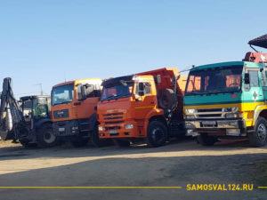Три грузовика и трактор на площадке по аренде техники